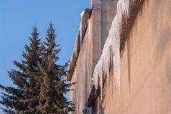 危险地垂悬从老房子屋顶的冰柱在冬天 免版税库存图片