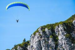 危险地飞行接近山峰的滑翔伞在一晴朗的秋天天 库存照片