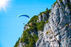 危险地飞行接近山峰的滑翔伞在一晴朗的秋天天 免版税库存图片