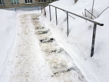 危险溜滑台阶和老扶手栏杆在冬天 库存照片
