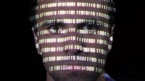 危险病毒的一个被聚焦的年轻黑客读的二进制ransomware代码的画象,当数据在他的面孔被射出-时 影视素材