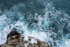 危险碰撞在与浪花和泡沫befor的岩石海岸的海波浪 库存图片