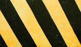 危险路标 在具体块纹理的黑和黄色条纹 免版税库存图片