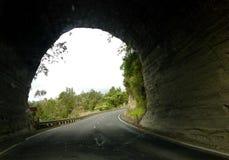 危险路通过隧道雕刻了在岩石外面山  库存照片