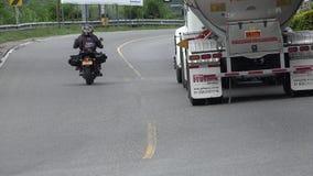 危险驾驶的摩托车和油卡车 免版税库存照片
