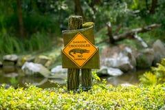 危险鳄鱼,没有游泳-位于湖的岸的警报信号 免版税图库摄影
