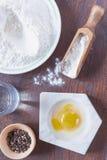 卵黄质和白色在碗,面粉在一把木匙子面粉 免版税库存图片