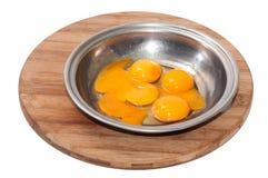 卵黄质和蛋白在一个碗在一个木板 免版税图库摄影
