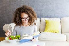 卷发十几岁的女孩阅读书和吃沙拉 库存图片