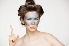 卷发夹和面部面具的皱眉年轻俏丽的裸体的女孩看在白色背景的照相机 秀丽skincare 免版税库存照片