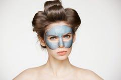 卷发夹和面部面具的皱眉年轻俏丽的裸体的女孩看在白色背景的照相机 秀丽skincare 免版税图库摄影