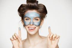卷发夹和面部面具的看照相机微笑在白色背景的年轻嫩女孩画象  beauvoir 免版税库存图片