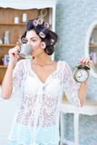卷发夹的美丽的妇女喝咖啡的早晨 免版税库存图片
