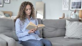 卷发妇女看书,当坐长沙发时