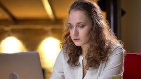 卷发的女实业家特写镜头画象殷勤地同时与膝上型计算机和智能手机一起使用在办公室 影视素材