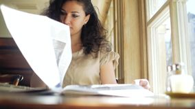 卷发的妇女在咖啡馆的一个窗口附近坐并且通过报纸生叶 股票录像