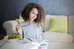 卷发青少年的女孩阅读书和吃沙拉 库存图片
