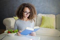 卷发青少年的女孩阅读书和吃沙拉 库存照片
