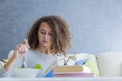 卷发青少年的女孩阅读书和吃沙拉 免版税库存图片