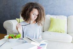 卷发青少年的女孩阅读书和吃沙拉 免版税库存照片