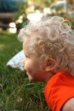 卷发,白肤金发,微笑的小孩户外在草在庭院里 免版税库存照片