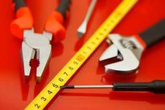 卷尺、螺丝刀、钳子和其他工具说谎在汽车修理店的红色优美的表面上 工作的设备  免版税图库摄影