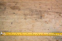 卷尺,在棕色木背景的卷尺 库存图片