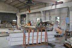 卷扬石材料的女工在工作室 免版税图库摄影