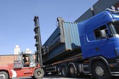 卷扬货物和发运集装箱的铲车 免版税库存图片