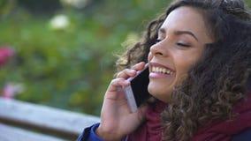 卷曲两种人种的妇女有效地谈话在智能手机,与朋友的交谈 股票视频