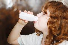 卷曲女孩为牛奶或酸奶喝着从瓶 Portrai 免版税库存图片