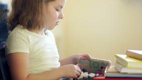 卷曲女孩合上书和快乐采取她的桃红色手机 在社会网络的通信 问题  股票视频