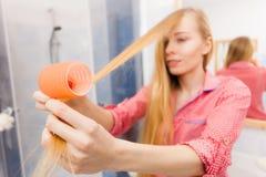 卷曲她的头发的妇女使用路辗 免版税库存图片