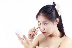 卷曲她的眼睛的亚裔妇女 免版税图库摄影