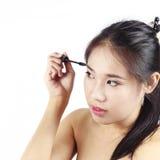 卷曲她的眼睛的亚裔妇女 库存照片