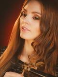 卷曲她长的棕色头发的愉快的妇女 库存图片