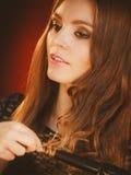 卷曲她长的棕色头发的愉快的妇女 免版税库存照片