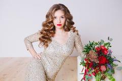 卷曲少妇画象闪烁金礼服的有完善的在白色背景的构成红色嘴唇的 概念 库存照片