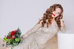 卷曲少妇画象闪烁金礼服的有完善的在白色背景的构成红色嘴唇的 概念 免版税库存照片