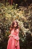 卷曲微笑的儿童女孩夏天画象桃红色童话公主礼服的在森林里 图库摄影