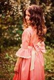 卷曲微笑的儿童女孩夏天画象桃红色童话公主礼服的在森林里 库存图片