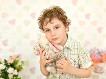 卷曲棕色目的男孩画象一件轻的米黄礼服的 免版税库存图片
