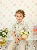 卷曲棕色目的男孩画象一件轻的米黄礼服的 免版税图库摄影
