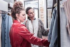 卷曲深色头发的妇女用帮助她的最好的朋友的头发小圆面包选择礼服 免版税库存图片