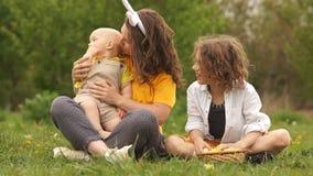 卷曲甜母亲和她的两个儿子在野餐的公园 愉快的复活节家庭 r 股票录像