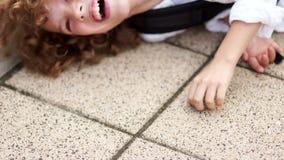 卷曲男小学生获得乐趣并且无所事事  男孩在沥青跌倒了并且敲他的在铺路石的拳头 股票录像