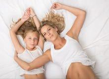 卷曲白肤金发的母亲和女儿在床一起放置 免版税库存图片