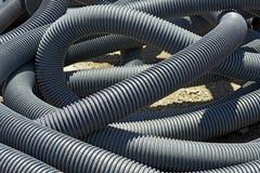卷曲的堆电子输送管道在露台建筑 图库摄影