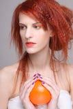 卷曲红发女孩用在她的现有量的桔子 库存图片