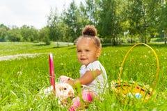 卷曲逗人喜爱的女孩用兔子在绿色公园 免版税库存图片